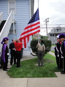 Grand Knight Ray Iacovone assists in the raising of the flag.