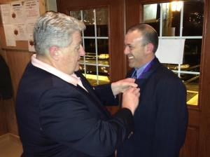 Grand Knight Ray Iacovone receives his Star Award pin from District Deputy Mike Walter.