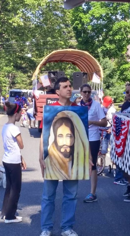 Dom Scarcella caries the image of Christ in the parade.